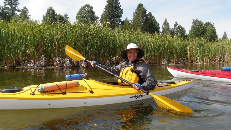 A woman kayaks down a river