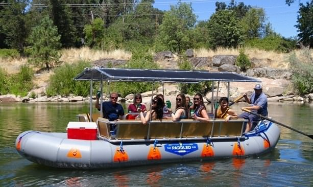 Guests motion cheers aboard a 20-foot inflatable raft
