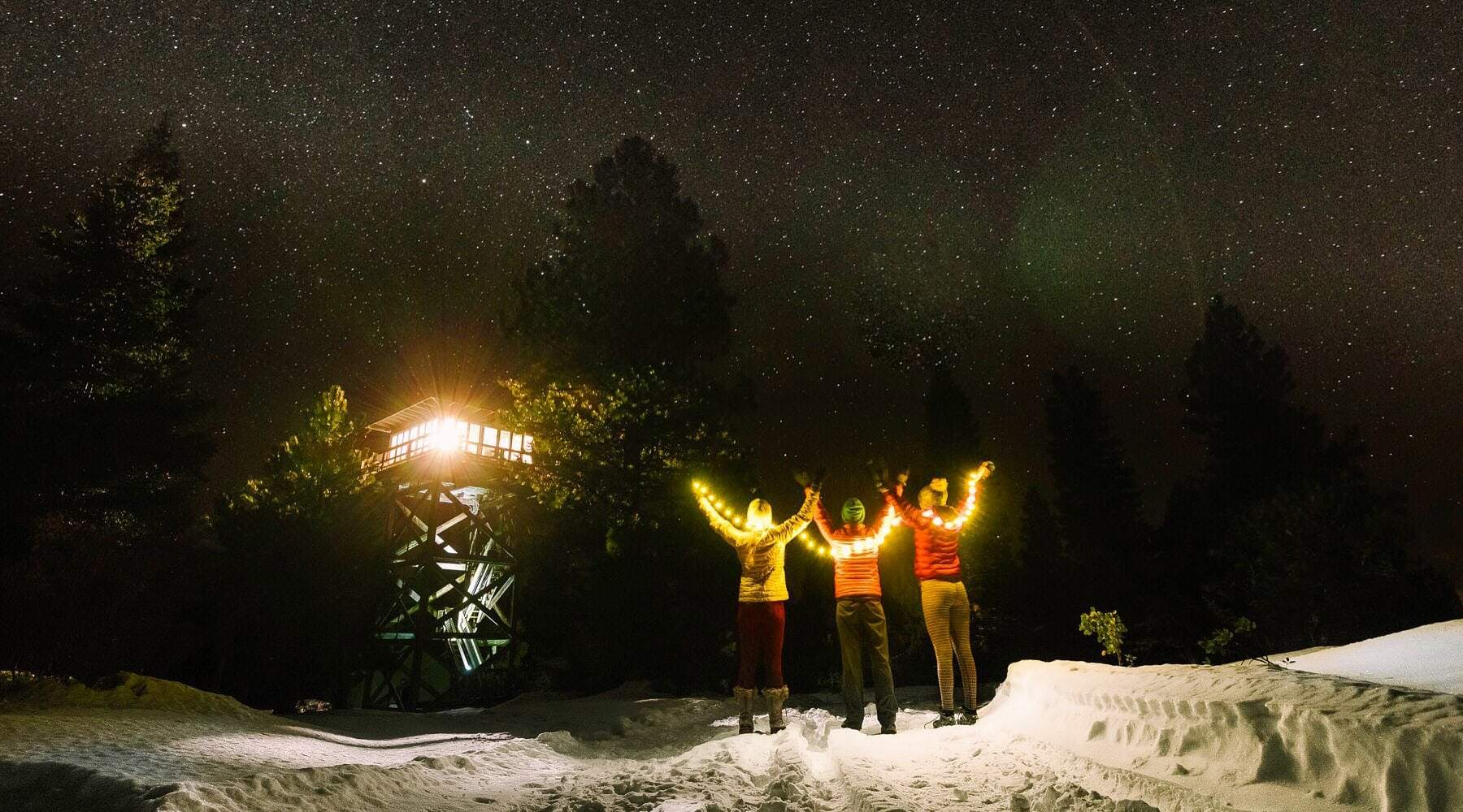 Friends holding lights in front of Fivemile Butte fire lookout at night in snow