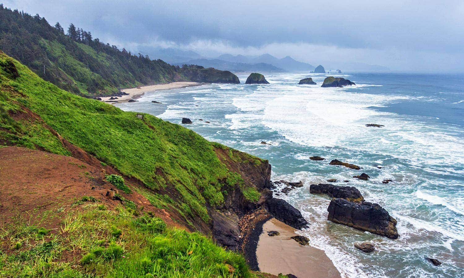 The view from an Oregon Coast headland reveals tree-lined hills along blue waters.