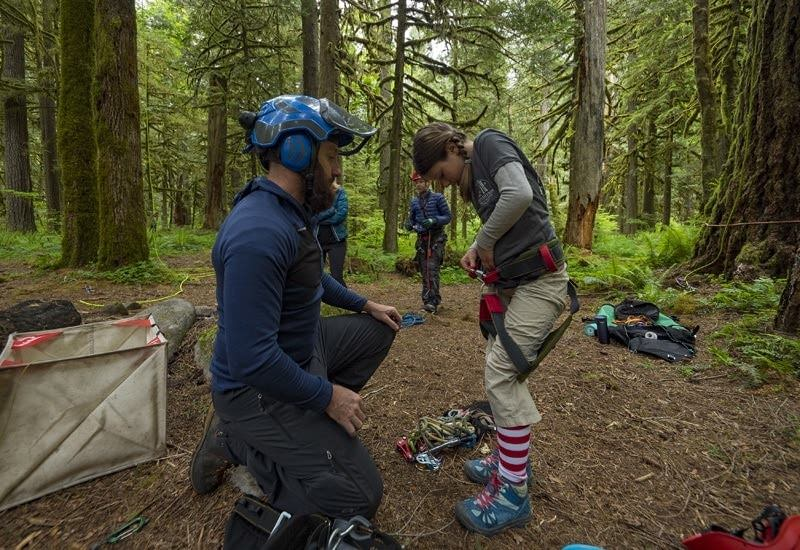 Expedition Old Growth leader helping kid into harness