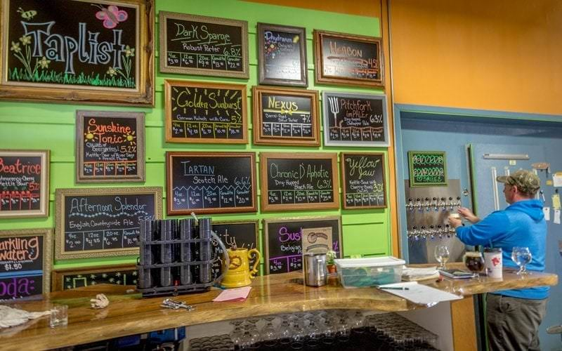 Bartender and colorful taplist at Agrarian Ales