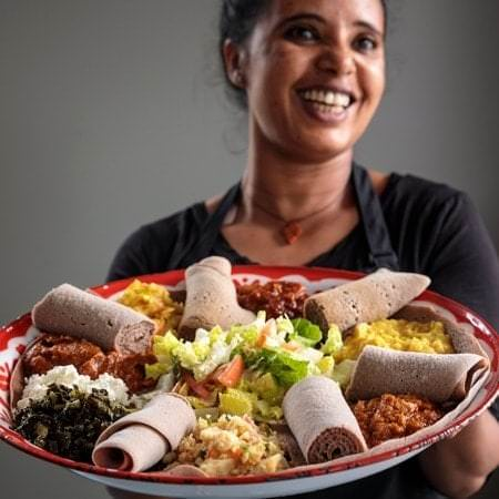 A smiling woman holds a plate of food to the camera.