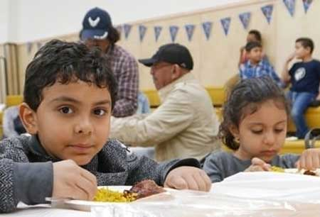 Two children eat at a community event.