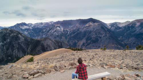 Man sitting on bench at top of Mt. Howard looking at the Wallowas
