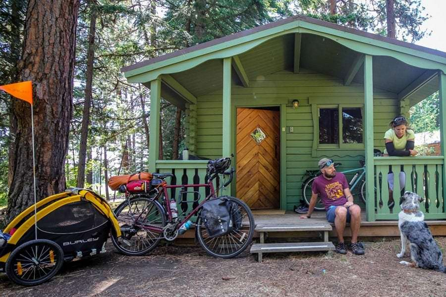 Bikepackers and dog outside green cabin at The Suttle Lodge