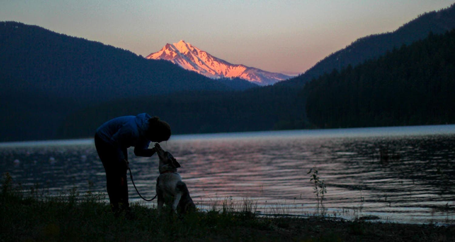 Jen kisses her dog Sora at Detroit Lake during sunset