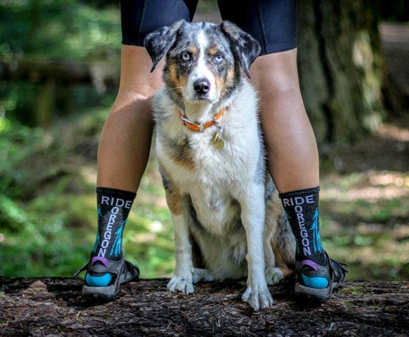 Dog peeks between legs of cyclist wearing Ride Oregon Ride socks