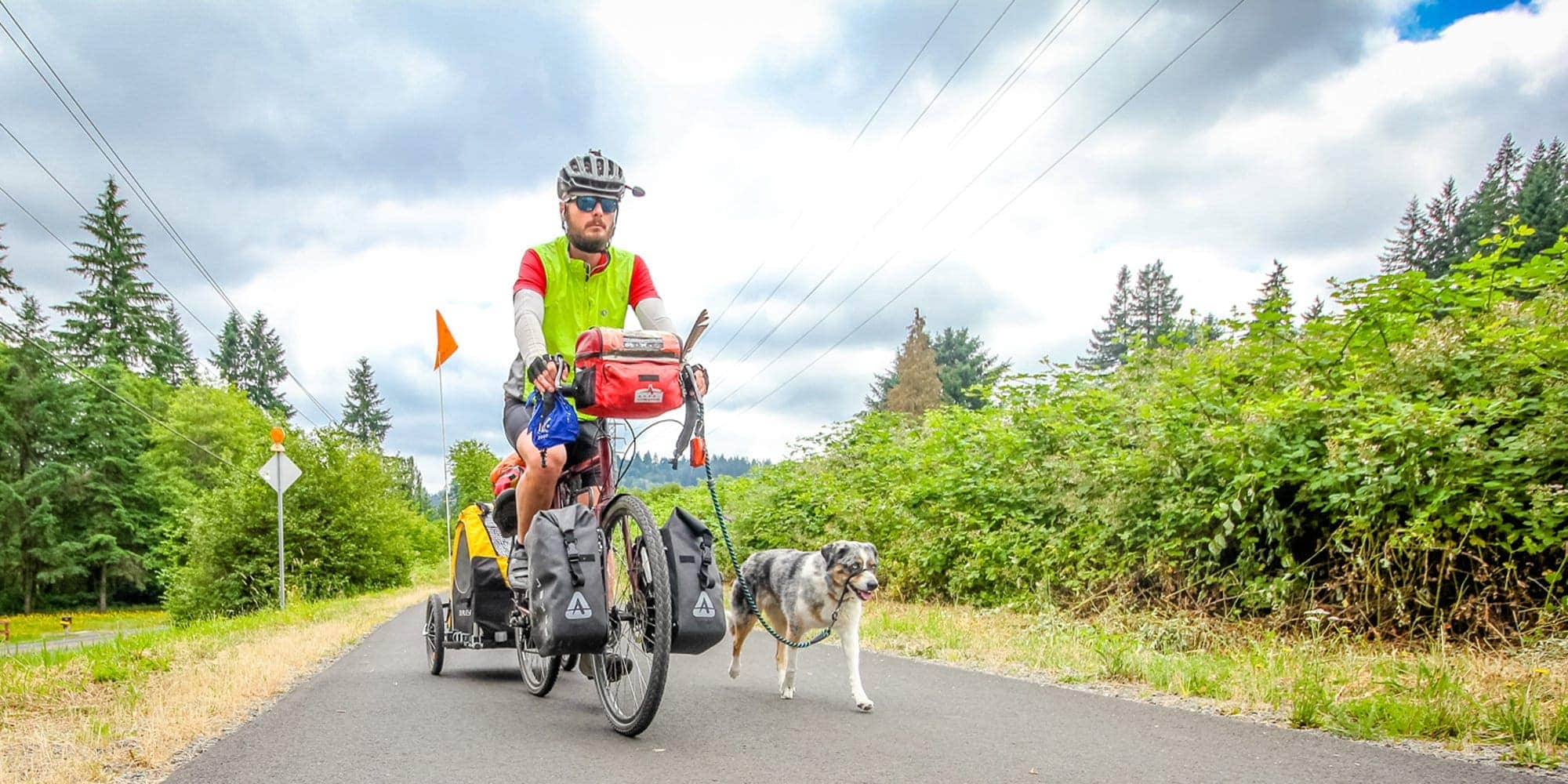 Cyclist riding with dog on leash on Springwater Trail near Portland