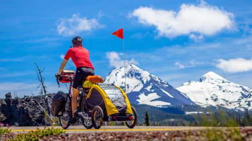 Cyclist towing dog trailer with snowy mountains in background