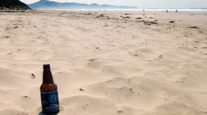 Bottle of Ninkasi Total Domination on the sand at Oregon beach