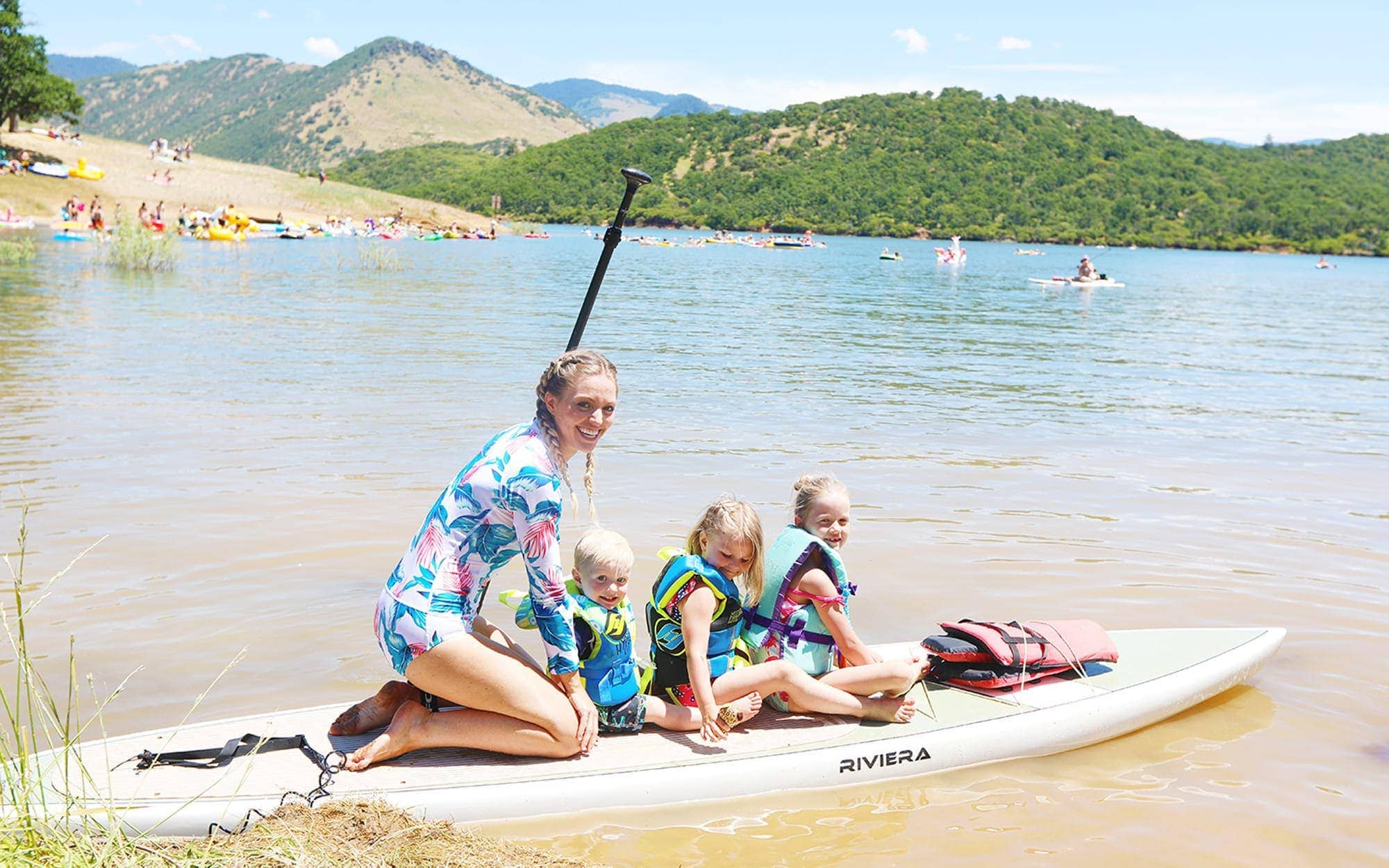 Mom and three kids wearing life vests on paddleboard at Emigrant Lake