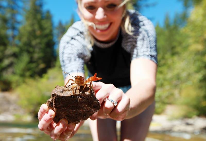 Woman holding rock with crawdad at Umpqua River