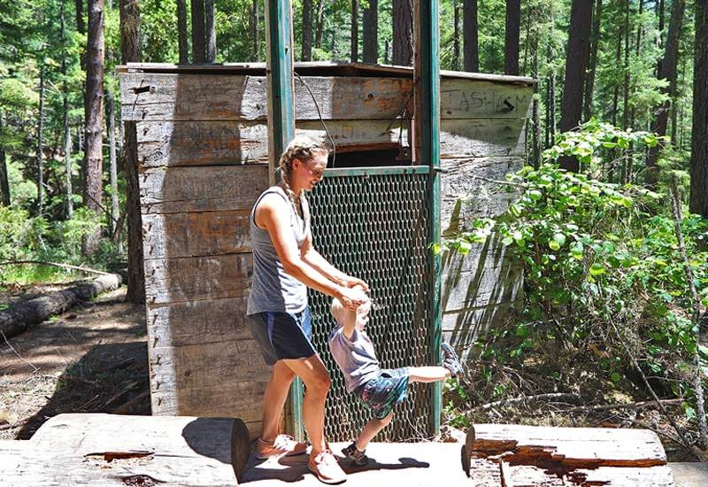 Mom swinging toddler son in front of Bigfoot trap