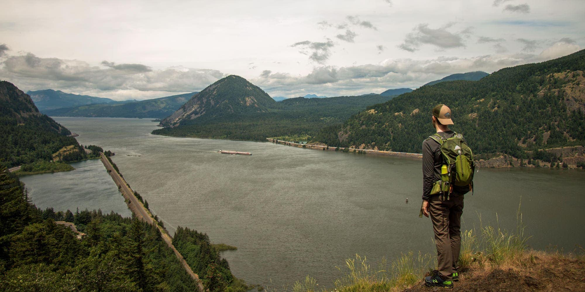 Man standing at viewpoint looking out at the vast Columbia River Gorge
