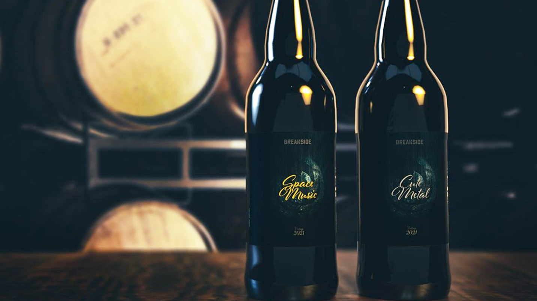 Two bottles of Breakside stout sit in front of barrels.