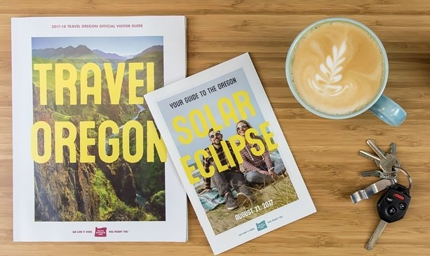 Travel Oregon guides, car keys and cup of coffee