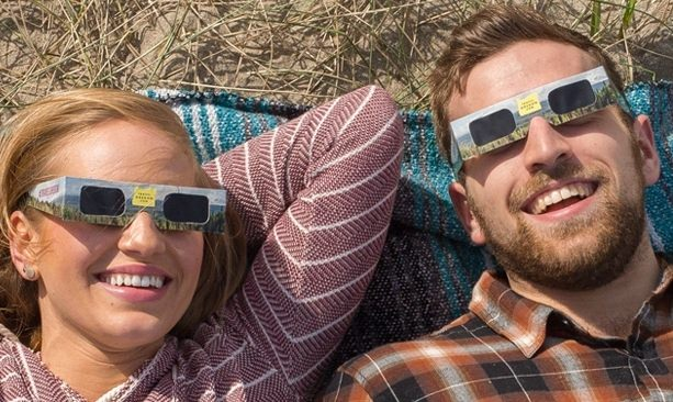 Couple wearing eclipse glasses