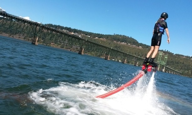 Man using flyboard above the Columbia River; Bridge of the Gods in the background