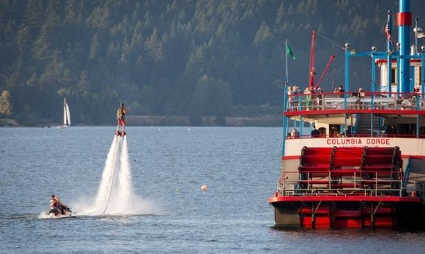 Flyboard user in the air next to the Columbia Sternwheeler; windsurfers in the background