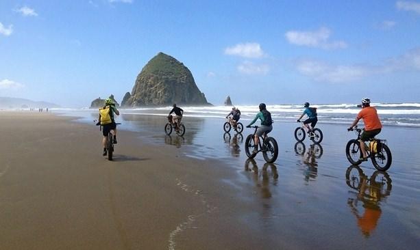 Fatbike cyclists near Haystack Rock in Cannon Beach