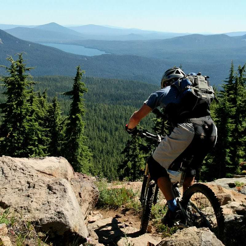 Mountain biker looks out to Cascade Lakes.