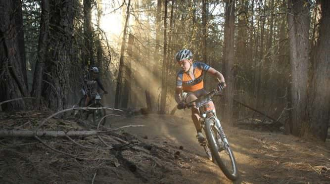 Female mountain bike pedals on singletrack.
