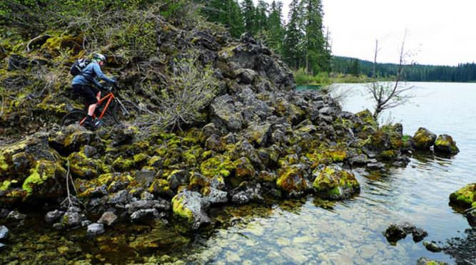 Mountain biker pedals past mossy rocks along McKenzie River.