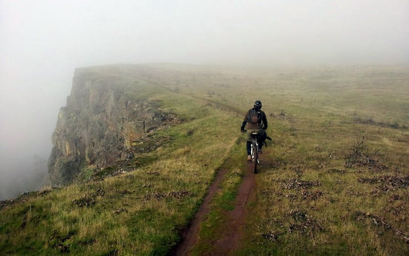 Mountain biker pedals through fog.