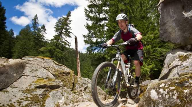 A mountain biker prepares to roll downhill a rocky terrain.