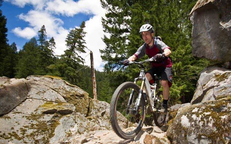 A mountain biker prepares to roll downhill a rocky terrain.