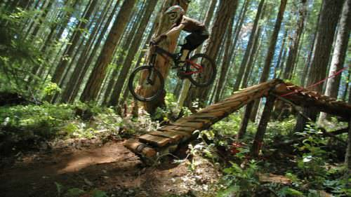 Mountain biker takes jump at Black Rock Mountain Bike Area.