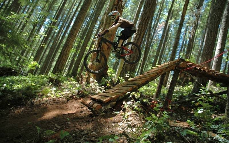 Mountain biker takes jump at Black Rock Mountain Bike Area.