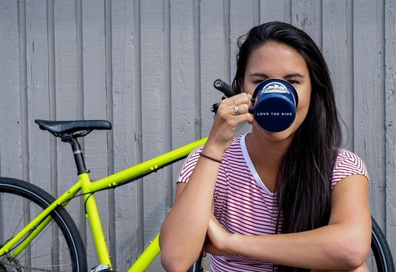 "Girl in front of bike drinks out of coffee cup that says ""love the ride."""