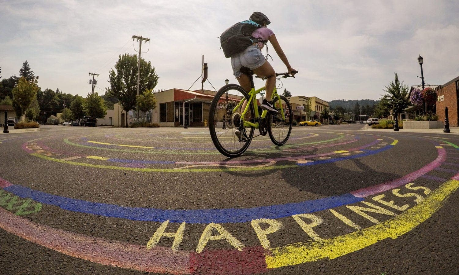 "Girl bikes over painted ground that says ""happiness."""