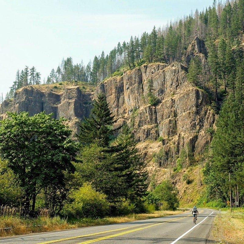 Big cliffs loom over bicyclists.
