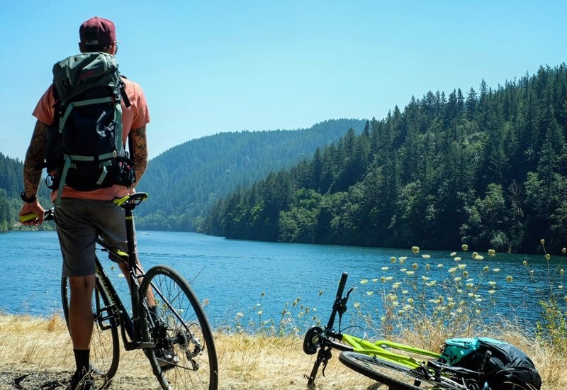 Cyclists peers out to blue lake.
