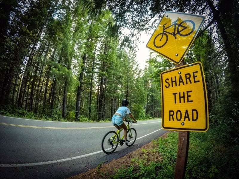 "Cyclist pedals past ""share the road"" sign near forest."