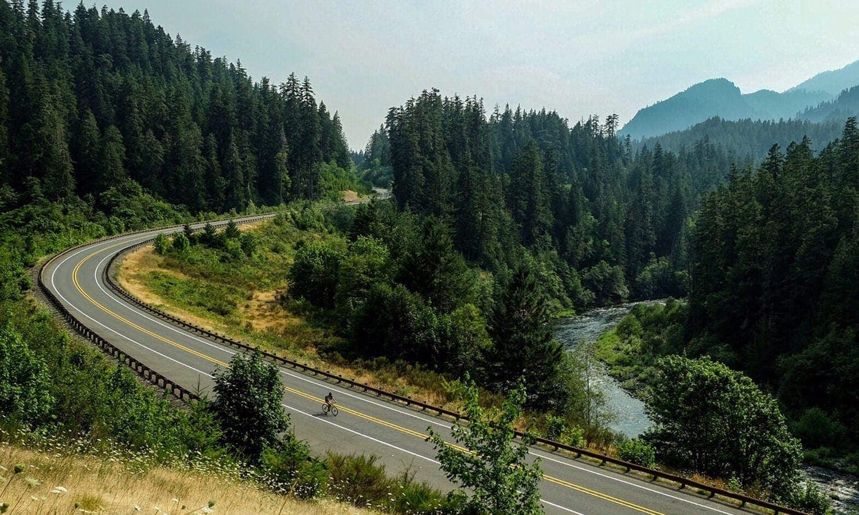 A bird's-eye view reveals cyclist going downhill near river.