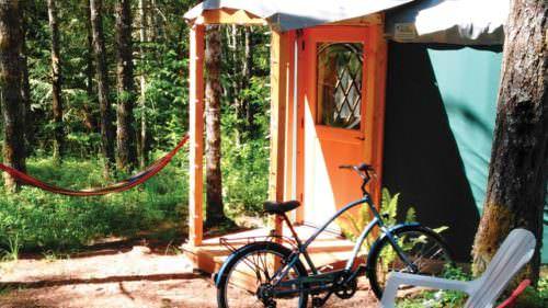 A hammock hangs outside a yurt.