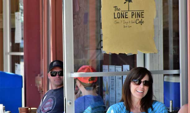 People mingle outside The Lone Pine Cafe on a sunny day.