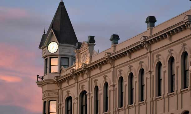 A pink sunset illuminates the windows of the historic Geiser Grand Hotel.