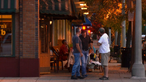 People on a sidewalk in the evening