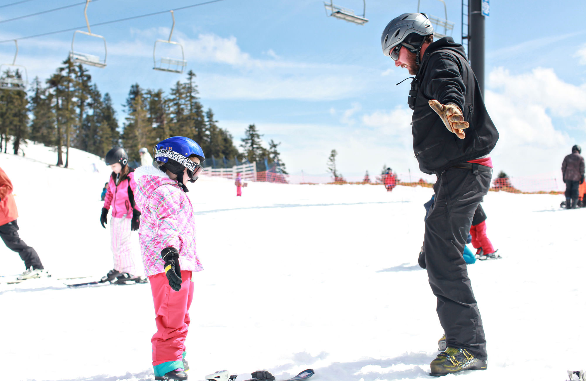 A little girl in a pink winter jacket is shown proper ski form by an instructor at Mt. Ashland.