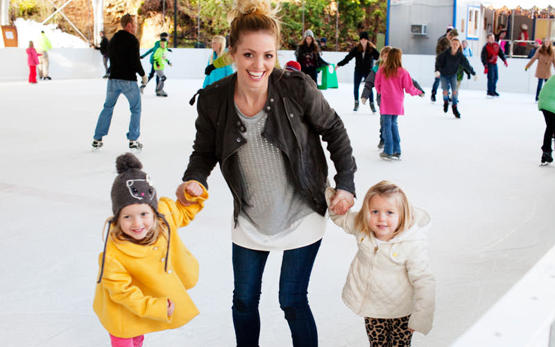 A smiling mother holds two little girls' hands as they ice skate.