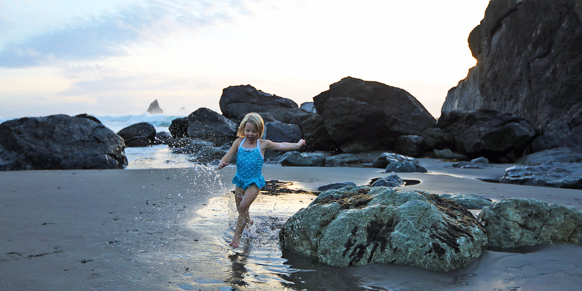 A little girl skips on the sand at the Oregon Coast.