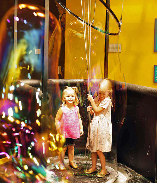 Two little girls stand inside a giant bubble.