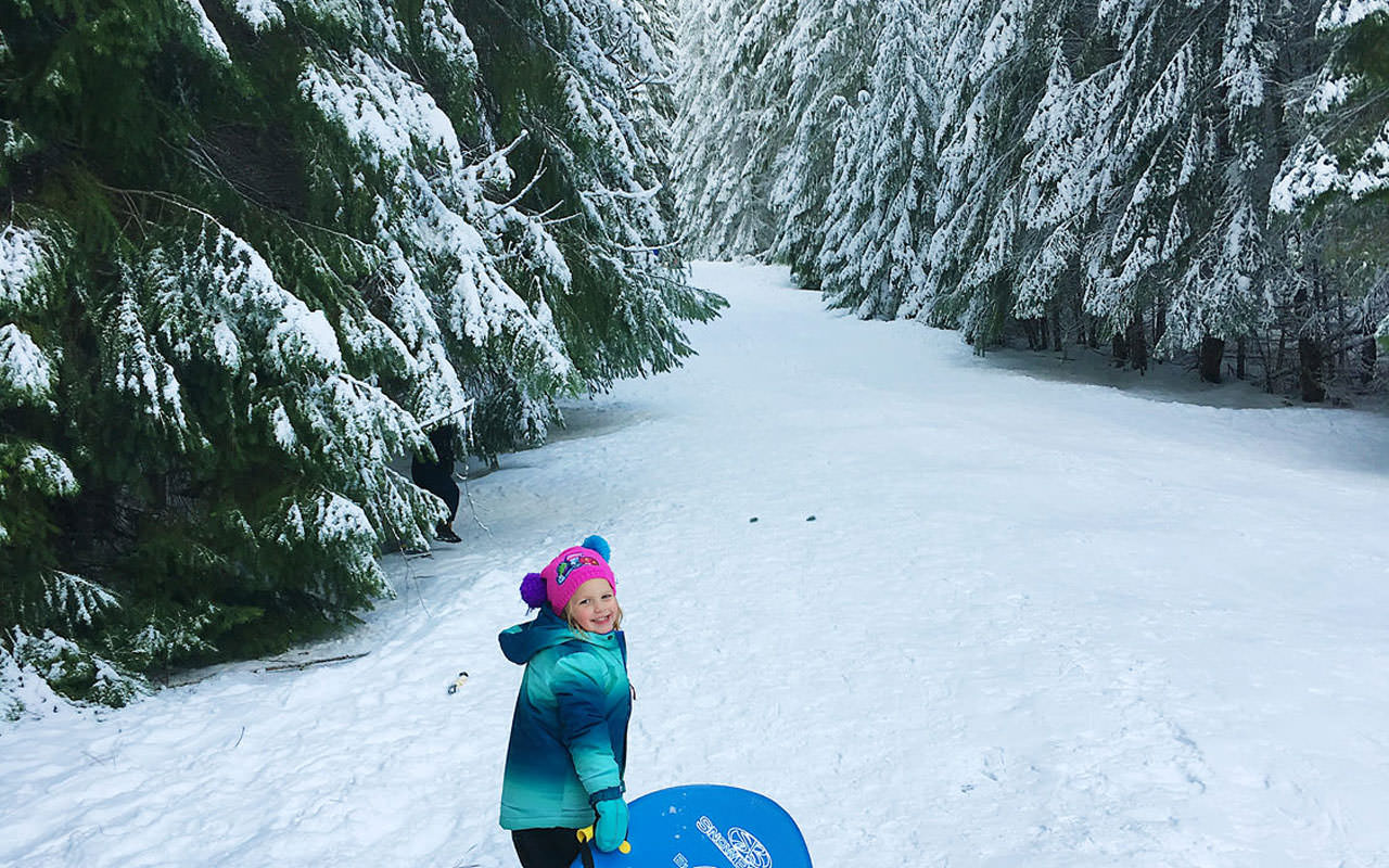 A little girl smiles as she pulls a sled on a snowy trail between trees.