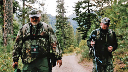 Scot Violette, director of Blue Mountain Bigfoot Research, left, hikes with Pete Nelson along a gravel Forest Service road in the Umatilla National Forest.