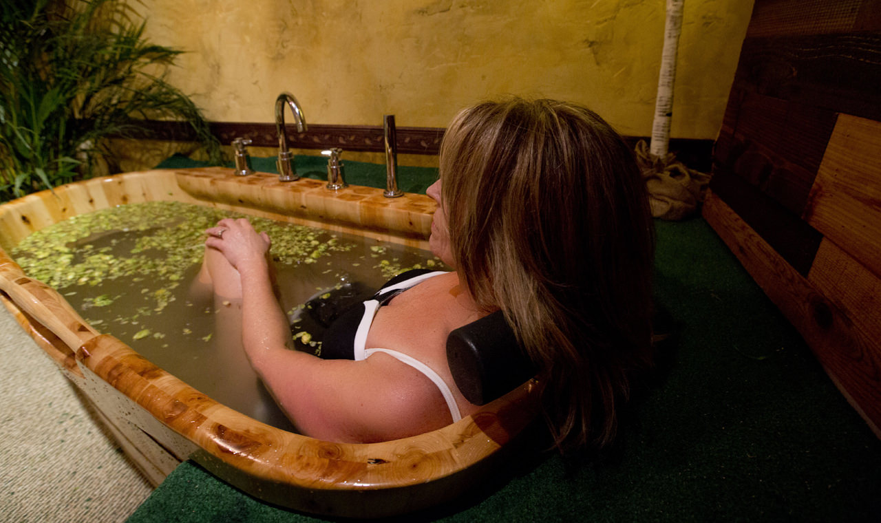 A woman soaks in a cedar tub filled with hops.